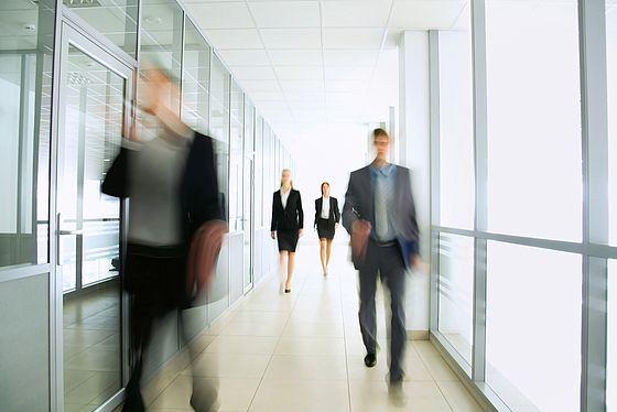 Geschäftsleute gehen einen hellen Flur entlang. Die Menschen sind stilistisch unscharf abgebildet.