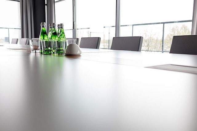 A close up of a conference table having a view out the window.