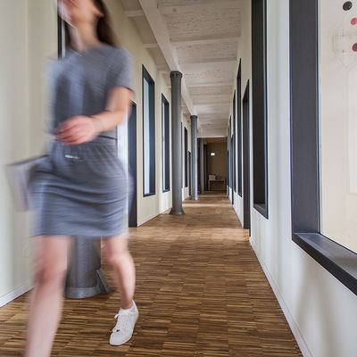 A women is walking down a bright hallway.