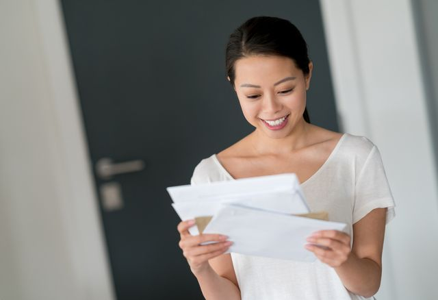 A young, smiling woman is reading a letter.