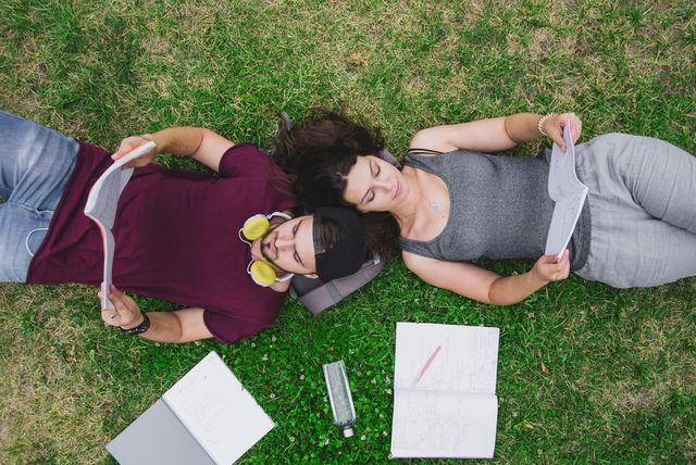 Two students are laying on the gras while studying.
