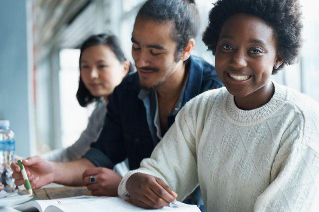 Eine junge, lächelnde Frau mit Buch im Fokus. Zwei weitere junge Menschen sitzen hinter ihr.
