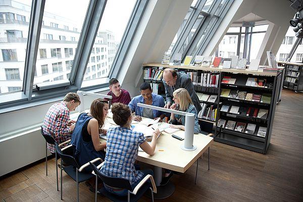 Eine Studentische Lerngruppe sitzt mit ihrem Tutor an einem Tisch in der Bibliothek.