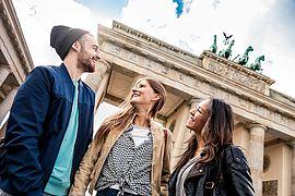 Drei Studenten stehen vor dem Brandenburger Tor in Berlin.