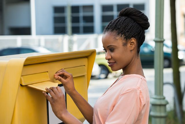 A young woman is inserting a letter into a letter box.