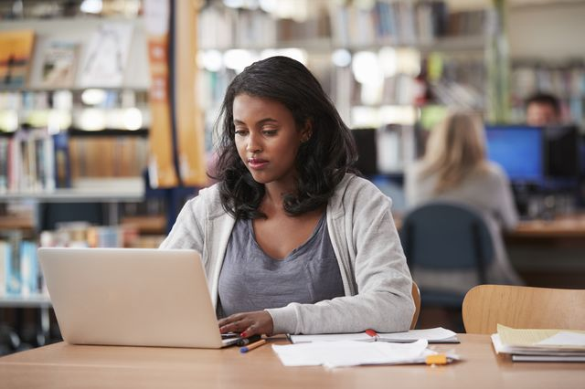 A young woman in a library is sitting in front of her laptop.