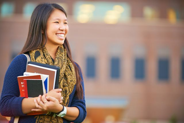 Eine junge Frau hält Bücher in der Hand.