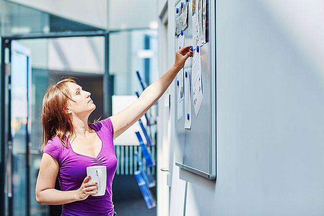 Junge Studentin greift nach einem Magneten an der Pinnwand.